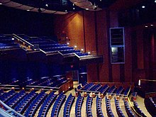 Theater with blue seats and wood paneled walls