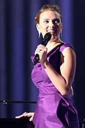 Johansson in a purple dress, standing next to a piano and holding a microphone