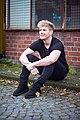 Schauspieler Adriaan van Veen sitzt und lächelt.jpg