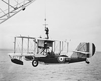 Single-engined military biplane with floats under wings being hoisted out of the ocean by a crane. A crewmen is riding on its top wing, holding the crane's cable.