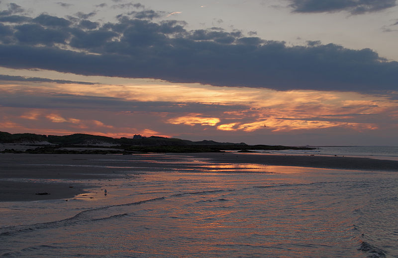 Sunset on the beach at Seahouses in Northumberland with Bamburgh Castle in the background. By mattbuck, freely licenced under CC BY-SA. Quality image, uploaded as part of Wiki Loves Monuments 2014.