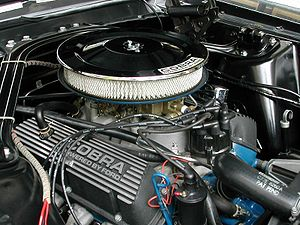 """Rocker cover - A Shelby Mustang Windsor V8 engine with """"Cobra Powered by Ford"""" labeled rocker (valve) cover (lower left)"""