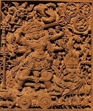 Tripurantaka - Here, the five headed Tripurantaka is seen pointing an arrow towards the Tripura (rightmost top corner) with the bow made of mount Meru, the serpent Vasuki is seen as its string. The four headed god Brahma is seen as the charioteer. The moon and the Sun are depicted as the wheels of the chariot.