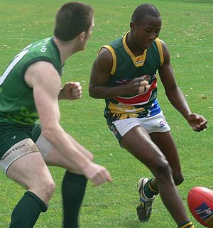 "Shepherding (Australian rules football) - Players from the Irish national team and South African national team prepare to bump each other.  Both have elbows and shoulders tucked in to execute a legal bump.  However only the South African has ""eyes for the ball"".  The Irish player, caught in a less advantageous position is instead ""playing the man"" and is attempting to take his opponent out."