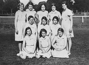 A black-and-white photo of a netball team. All the girls in the picture are school aged, wearing white and have their netball skirts on.