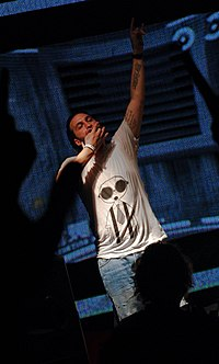 A light-skinned man is dressed in a short-sleeved shirt and is seen performing in a dark room.
