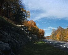 A divided highway going past a rock outcrop in autumn