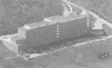 A black-and-white aerial photograph of a long, narrow six-story building