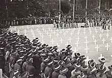 Soldiers in slouch hats stand around a square of white crosses during a ceremony at a war cemetery