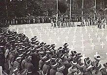 Soldaten in Schlapphuten stehen wahrend einer Zeremonie auf einem Kriegsfriedhof um ein Quadrat aus wei?en Kreuzen