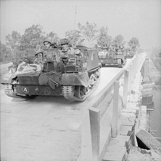 Grenadier Guards - Universal Carriers of the 1st Battalion, Grenadier Guards cross 'Euston Bridge' as they deploy for Operation 'Goodwood', 18 July 1944.