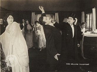 The Yellow Passport - Clara Kimball Young reacts as John St. Polis is punched by Edwin August in a scene still from the 1916 silent drama The Yellow Passport.