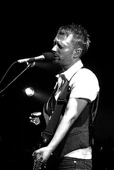 Black and white image of a man wearing a white dress shirt, a dark vest and jeans holding a guitar and standing behind a microphone stand. His eyes are closed, and the background is completely black except for a single light that shines from behind.