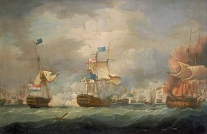 On a stormy sea beneath towering clouds, a number of sailing warships battle. In the foreground are three ships, two to the right of the frame bridged by clouds of smoke and the mainmast of the far right ship, which bears a prominent horizontally striped flag is toppling. To the left of the frame a third ship drifts as flames leap from its deck.