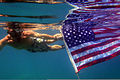 U.S. Navy Petty Officer 2nd Class Geoff Shepelew, 221st Explosive Ordnance Disposal Mobile Unit 2, holds the American flag while swimming during Shepelew's scuba diving re-enlistment off the coast of Moucha 120212-F-YO139-303.jpg