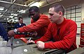 US Navy 030327-N-1328C-504 Airman Apprentice Warren James (left) torques down a set screw on a 2,000-lb GBU-12 laser guided bomb as Aviation Ordnanceman 1st Class Jonathan Boyd looks on as a safety observer during the procedure.jpg