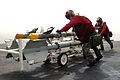 US Navy 030327-N-6817C-029 Aviation Ordnancemen move AIM-9 Sidewinder air-to-air missiles to nearby aircraft aboard USS Abraham Lincoln (CVN 72).jpg