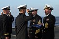 US Navy 030415-N-5555F-017 Capt. Michael C. Manazir, Commanding Officer of the fast combat support ship USS Sacramento (AOE 1), is saluted by a flag bearer during a burial at sea ceremony.jpg