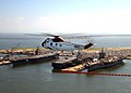 US Navy 040827-N-4459K-002 A UH-3H Sea King helicopter assigned to the Search and Rescue (SAR) unit at Naval Air Station Oceana, Va., flies over the aircraft carriers moored at Naval Station Norfolk, Va.jpg