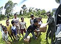 US Navy 050119-N-2560Y-122 Aviation Structural Mechanic Airman Michael Stewart assigned to Helicopter Combat Support Squadron Eleven (HC-11), off-loads supplies to waiting children in Banda Aceh.jpg