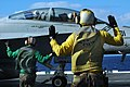 US Navy 050711-N-4321F-097 Aviation Boatswain's Mate 2nd Class William Tanner, foreground, gives the signal for hands off to the aircrew of an F-A-18F Super Hornet.jpg