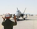 US Navy 050730-M-5865P-084 A U.S. Marine assigned to Marine Fighter Attack Squadron Three Three Two (VMFA-332) signals the pilots of a F-A-18 Hornet.jpg