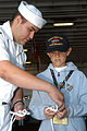US Navy 050803-N-7048B-047 Seaman Nick Contreras demonstrates the art of knot tying for a young embarked guest aboard the amphibious assault ship USS Bonhomme Richard (LHD 6) during the 55th annual Seafair Festival parade of sh.jpg