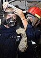 US Navy 080729-N-4221W-002 Damage Controlman 3rd Class Sarah Thomas helps Electrician's Mate 3rd Class Mike Tilley put on his personal protective equipment.jpg