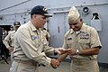 US Navy 081003-N-9818V-198 Capt. Patrick Scanlon, commanding officer of the submarine tender USS Frank Cable (AS 40), presents Master Chief Petty Officer of the Navy (MCPON) Joe R. Campa Jr. with a ship's coin during an all-han.jpg