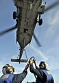US Navy 090829-N-2638R-005 oatswain's Mate Seaman Tiffany Walker and Seaman Adam Komperda attach a load to an MH-60S Sea Hawk helicopter.jpg