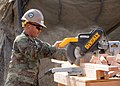 US Navy 091007-N-1424C-180 Builder 3rd Class Jermaine Takai, assigned to amphibious construction Bbttalion ONE (ACB-1) uses a miter saw to cut lumber for the construction of a life support area (LSA) for 800 military personnel.jpg