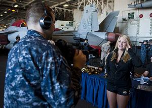 US Navy 120131-N-FI736-056 Mass Communication Specialist 2nd Class Nathan Carpenter interviews a Jacksonville Jaguar cheerleader in the hangar bay.jpg