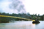 Riverboat of the U.S. brownwater navy firing napalm at an onshore target during the Vietnam War.