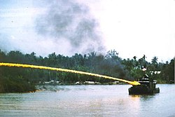 Riverboat of the U.S. Brownwater Navy shooting ignited napalm from its mounted flamethrower during the Vietnam war.
