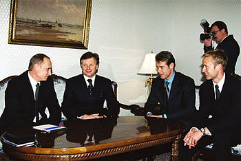 Four men in suits, two middle-aged and two in their thirties, sit smiling around a glossy wood table. A photographer hovers in the background.