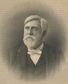 A white-haired man with a beard and mustache, facing left. He is wearing a white shirt, black vest and black jacket