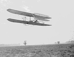 Wright Flyer II - Wilbur in Flyer II circling Huffman Prairie in November 1904. The front elevator has been enlarged and the radiator moved to a rear strut.