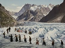 hundred year old postcard showing a group of people walking across a glacier