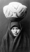 Zuni Girl with Jar, c. 1903. Head-and-shoulders portrait of a Zuni girl with a pottery jar on her head.