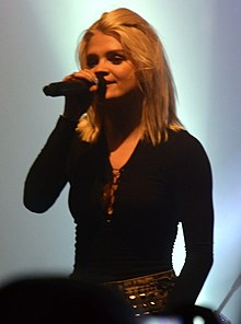Margaret performing on stage wearing black top and holding a microphone in her hand.