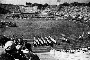 A black-and-white photograph of a stadium with athletes marching at the track