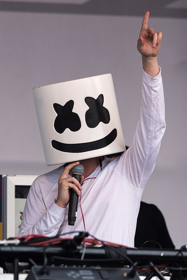 Marshmello holding a mic in his right hand and raising another hand in the air
