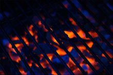 A greasy barbecue grill with the glow of coals behind.jpg