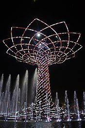 Large tree made of lights at night, surrounded by fountains