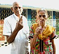 An elderly couple voters showing mark of indelible ink after casting their votes, at a polling booth, during the Bihar Assembly Election, in Gaya on October 16, 2015.jpg