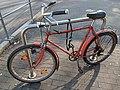 Angeschlossenes, altes, rotes Fahrrad.jpg