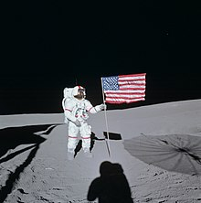 A astronaut in an Apoloo space suit with red ring markings on the arms and legs and a red stripe down his helmet stands amid grey dust, holding a crumpled American flag on a flagpole