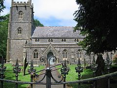 Gray stone building with square tower at left hand end. Foreground includes grass area with gravestones, taken over the top of metal railings.