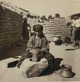Assyrian woman pounding Burghul.jpg