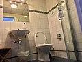 Bathroom in hotel in Bergen, Norway. 2016-03-16. hand wash basin sink, mirror, toilet, shower cabinet, etc (low view). Also wall and floor tiles.jpg